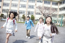 Japanese school children running out in the yard