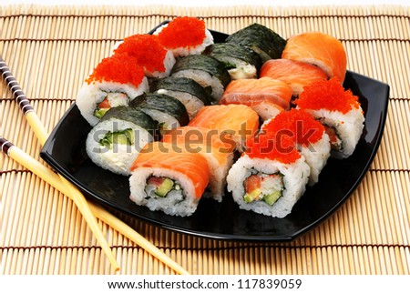 Japanese seafood, rolls on a black plate