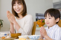 Japanese Son and mother putting palms together before eating