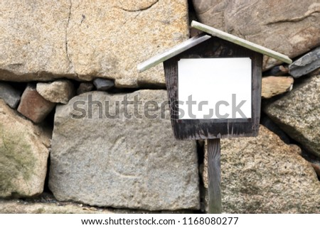 Japanese style old grunge vintage wooden notify billboard showing outside a temple, with strong stone wall as background.