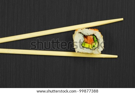 Japanese sushi and sticks isolated on black wooden board - stock photo