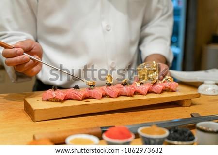 Japanese Sushi Chef making Blue Fin Otoro Sushi. Omakase sushi course. Selective focus on sushi.