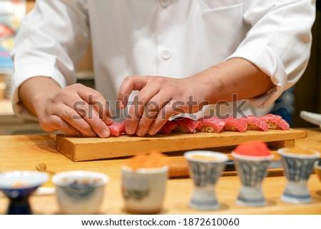 Japanese Sushi Chef making sushi. Omakase sushi course. Selective focus on sushi.
