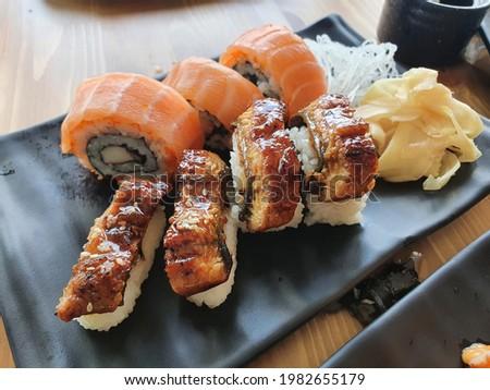 Japanese sushi food. Maki ands rolls with tuna, salmon. Top view of assorted sushi. Rainbow sushi roll, uramaki, hosomaki and nigiri.Assortment of different kinds of sushi rolls
