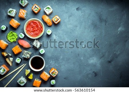 Japanese sushi on a dark background. Sushi rolls, nigiri, maki, pickled ginger, wasabi, soy sauce. Sushi set on a table. Space for text. Top view. Sushi background. Asian or Japanese food frame. Toned