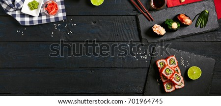 Japanese sushi rolls and gunkan sushi set with salmon shrimp sesame and cream cheese on stone slate with chopsticks and lemon with soy sauce and ginger on dark wooden copyspace background.