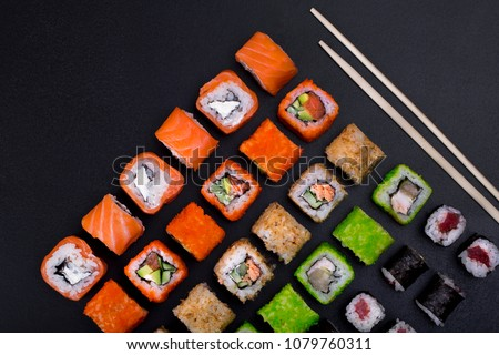 Japanese sushi rolls in the shape of a line on black background top view