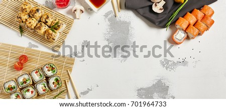 Japanese sushi rolls set with salmon and cream cheese and hot deep fried on bamboo napkin with chopsticks and cherry tomatoes with soy sauce and ginger on white rustic copyspace background.