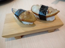 Japanese sushi, two pieces of foie gras on top of sticky rice and tide with seaweed line, served on bamboo traditional dish on wood table, in local restaurant. As attractive place for food tours.