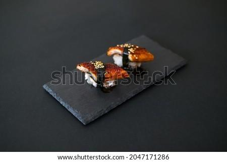 Japanese Sushi - Two Unagi Nigiri Sushi on black stone board. Sushi pieces served on black slate isolated on black background. Sushi with backed eel