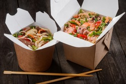 Japanese takeaway food packaged in special boxes. Chopsticks and portions of noodles with chicken meat and rice stirred with vegetables, seafood and soy sauce, then fried in wok.