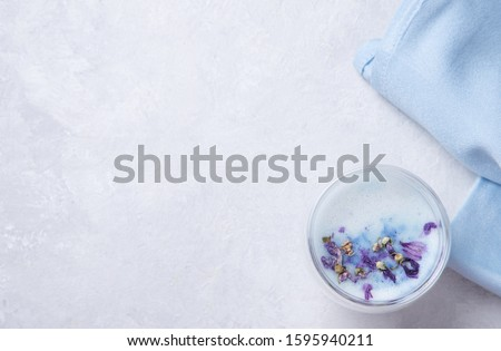 Japanese tea blue matcha from clitoris flowers with milk in a transparent glass on a white background. Top view and copy space