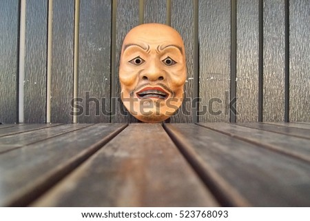 Japanese theater masks made of wooden on brown wood background,male mask