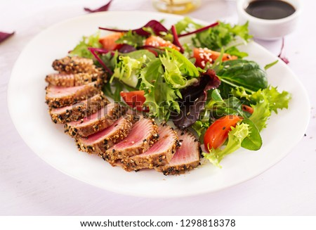 Japanese traditional salad with pieces of medium-rare grilled Ahi tuna and sesame with fresh vegetable salad on a plate. Authentic Japanese food.