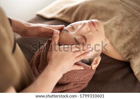 Japanese woman receiving a facial massage at an aesthetic salon Photo stock ©