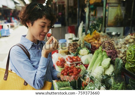 Japanese woman smelling cherry tomatoes at market counter