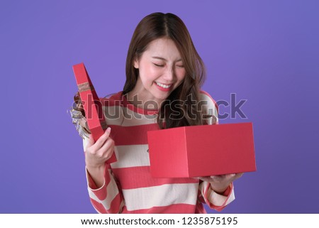 Japanese woman surprised while opening the gift box, winter t-shirt clothing, purple background