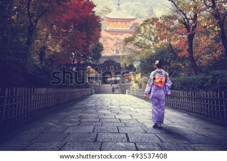 Japanese woman walking to red pagoda, Japan