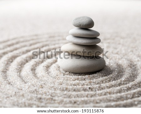 Japanese zen garden meditation for concentration and relaxation. Sand circles in spiral and rocks for harmony and balance in pure simplicity. Macro lens shot.