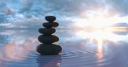 Japanese zen garden - stacks of pebbles in the wide ocean at sunset