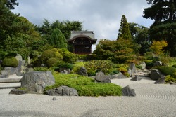 japanese zen garden with pagoda in background surrounded by shrubs and trees and sand in forground