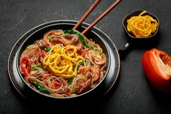 Japchae in black bowl on dark slate table top. Korean cuisine glass chapchae noodles dish with vegetables and meat. Asian traditional food. Authentic meal