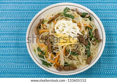 Japchae - Stir fried Korean sweet potato noodles with vegetables, mushrooms and beef garnished with slices of fried egg and sesame seeds.