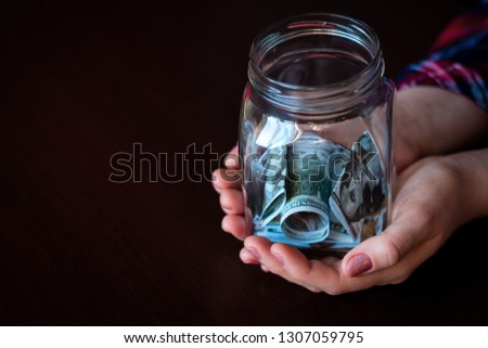 jar for donation, fundraising, charity with money, on a black background with space for text #1307059795