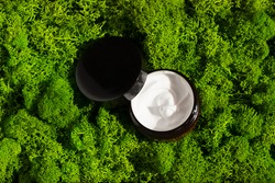 Jar of beauty cream on green moss background in the morning rays of light. Organic clay mask cream for the face and body. Concept of skincare cosmetic, spa and wellness center, facial treatment