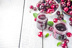 Jar of cherry jam. Homemade sweet and sour cherry jam with fresh cherries on wooden white table, copy space