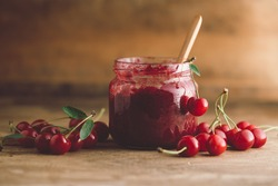 Jar of cherry jam, sour cherries and spoon