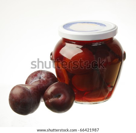 Jar of conserved plum and some fresh plums