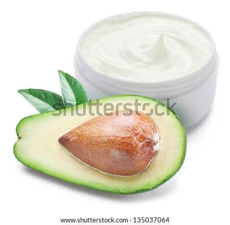 Jar of cream and slices of avocado on a white background.