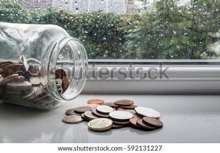 Jar of english money with rainy day background
