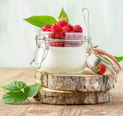 Jar of fresh homemade yogurt with fresh raspberries ripe for breakfast on a wooden background. The concept of healthy natural foods. selective Focus