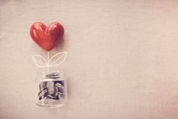 Jar of heart plant growing on money coins, CSR social responsibility,  donation, economic restoration post  coronavirus covid-19 pandemic crisis, stimulus relief recover plan for reopen business