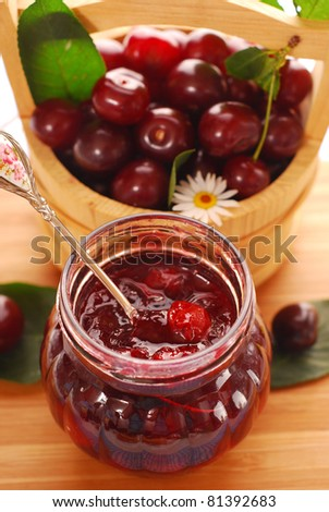 jar of homemade cherry confiture and basket with fresh fruits