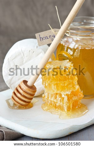 Jar of honey, delicious honeycombs and camembert on a wooden board.
