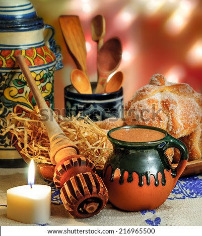 Jar of hot chocolate and sweet bread (pan de muerto) with wooden chocolate grinder and spoons on festive background  Foto stock ©