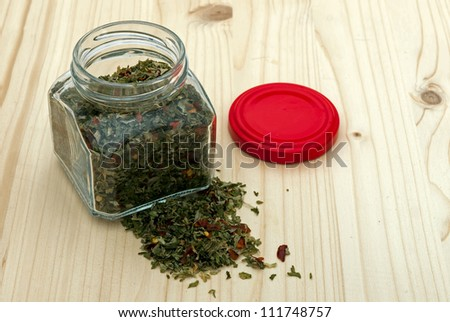 Jar of mixed herbs on wood background
