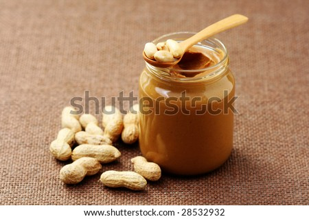 jar of peanut butter with spoon - food and drink