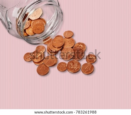 Jar of pennies spilling out on refective white