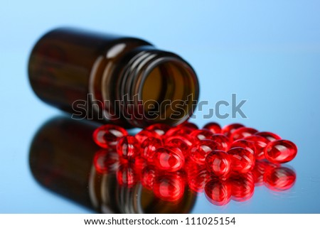 Jar of pills on blue background close-up