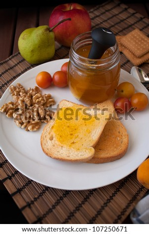 Jar of plums jam with toasted bread, walnuts and fruits in a dish