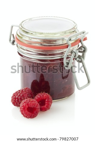 jar of raspberry jam, three fruit in front, white background