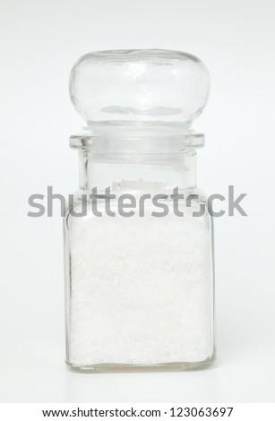 jar of sea salt over white