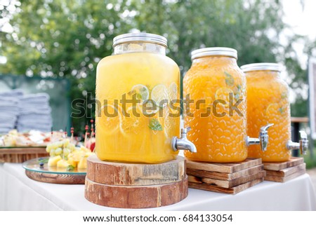 Jar of tasty fresh orange lemonade with ice and mint.