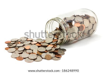 Jar of US coins spilled on a white background