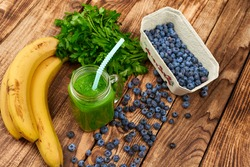 Jar tumbler mug with green smoothie drink and a bundle of fresh parsley, banana and blueberries on wooden table