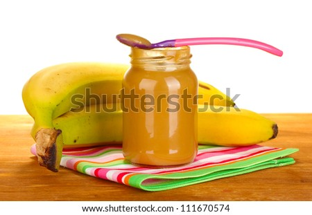 Jar with banana baby food, spoon and bananas on colorful napkin on white background close-up